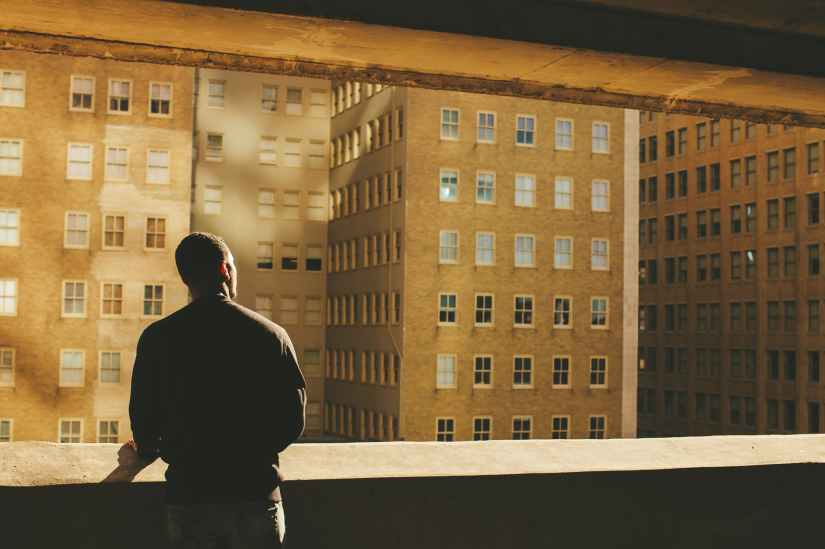 man standing on rooftop facing brown highrise building